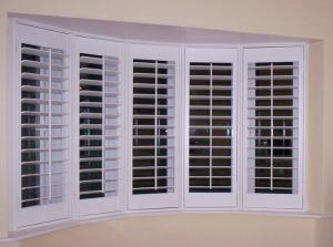 Curved bay window with five sections and plantation shutters