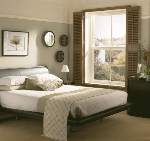 Stylish wood stained shutters in bedroom