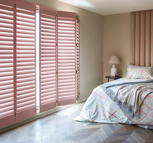 Beautiful floor to ceiling custom painted bedroom shutters
