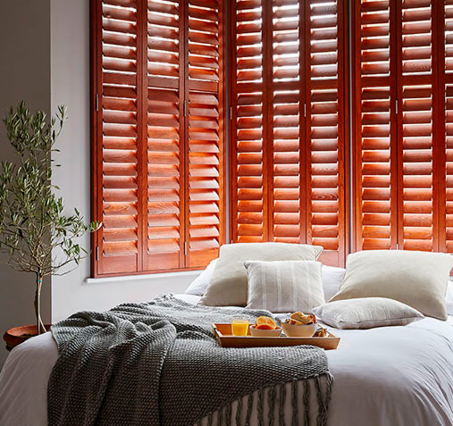wood stained bedroom shutters
