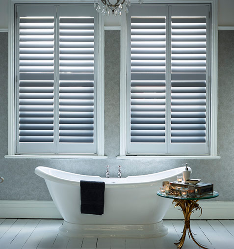 Chic grey slatted bathroom shutters with free standing tub