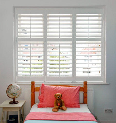 childrens room with teddy bear, globe and white shutters
