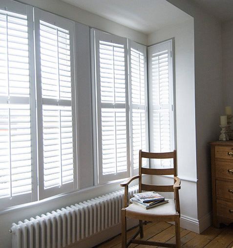 A cosy shabby chi bedroom with white bay window shutters