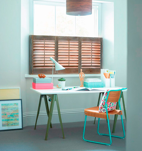 Natural wood stained shutters in home office space
