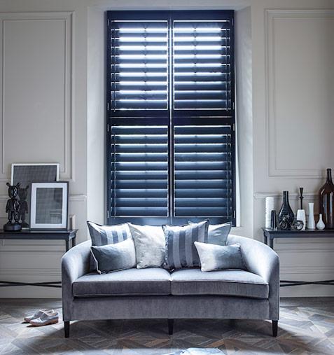 Light filtering through blue window shutters in lounge