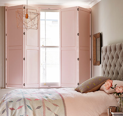 Perfectly styled cosy bedroom with bright light in from shutters