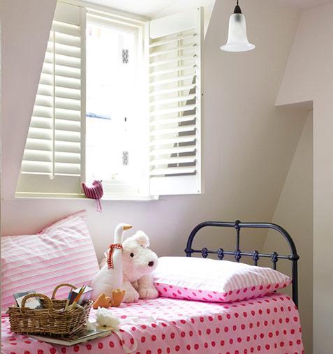 Pink bedspread in children's nursery with window shutters